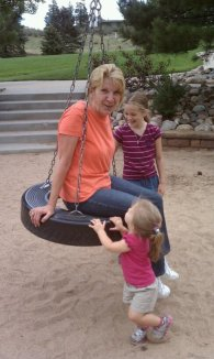 My girls pushing their grandma on the tire swing.